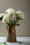 Fleurs blanches dans le broc sur la table en bois photographie stock libre de droits