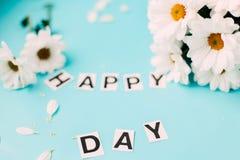 fleurs blanches de jour heureux, lettres HEUREUSES Photo stock