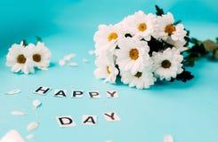 fleurs blanches de jour heureux, lettres HEUREUSES Photos stock