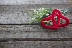 Fleurs blanches et deux coeurs sur un fond en bois Photographie stock libre de droits