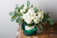 Fleurs blanches mélangées Bouquet des roses et des ranunculuses de jet dans une boîte sur la table en bois Copiez l'espace Blanc  Image libre de droits