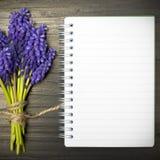 Fleurs bleues et carnet vide Photographie stock libre de droits