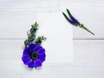 Fleurs bleues et feuille blanche sur le fond en bois Image stock