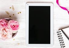 Fleurs, bloc-notes et comprimé avec l'écran vide Photo stock