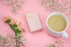 fleurs, boîte-cadeau et tasse de boisson sur un fond rose vibrant images libres de droits