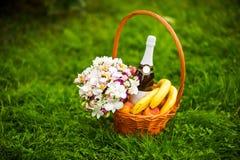 Fleurs, champagne et fruit dans un panier Photographie stock libre de droits