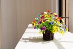 Fleurs colorées en panier en bois de Brown près de vitrail Images libres de droits