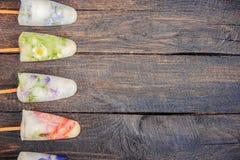 Fleurs congelées en glaçons et crème glacée sur un bâton Photo stock