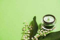 fleurs cosmétiques de crème et du muguet sur un fond vert photos libres de droits