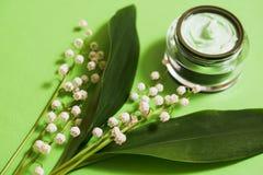 fleurs cosmétiques de crème et du muguet sur un fond vert photo stock
