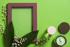 fleurs cosmétiques de crème et du muguet sur un fond vert images libres de droits