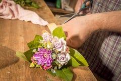 Fleurs coupées en gros plan d'homme avec des ciseaux dans un fleuriste Images libres de droits