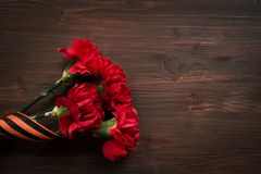 Fleurs d'oeillet et plan rapproché de George Ribbon sur un fond foncé Jour de victoire - 9 mai Jubilé 70 ans Photographie stock libre de droits