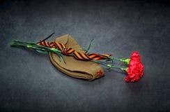 Fleurs d'oeillet, George Ribbon et chapeau de garnison militaire Photographie stock libre de droits