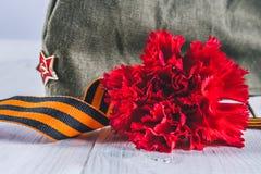 Fleurs d'oeillet, George Ribbon et chapeau de garnison militaire avec une étoile rouge 9 mai Victory Day Photographie stock libre de droits