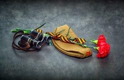 Fleurs d'oeillet, George Ribbon, jumelles militaires et chapeau de champ Images stock