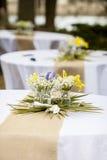 Fleurs dans des pots de maçon sur des tables Photographie stock