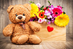 Fleurs dans la boîte et un ours de nounours Photo libre de droits