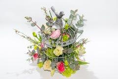 Fleurs dans la cage d'oiseaux sur le fond blanc Photo stock