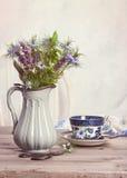 Fleurs dans la cruche antique avec la tasse de thé Photo stock