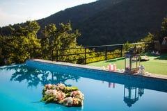 Fleurs dans la piscine, les lanternes noires et blanches et les bougies près de la piscine Image libre de droits
