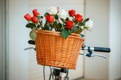 Fleurs dans le panier accrochant aux guidons de bicyclette Photo libre de droits
