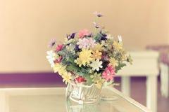 Fleurs dans le panier blanc sur la table Image stock