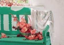 Fleurs dans le panier sur le banc Images stock