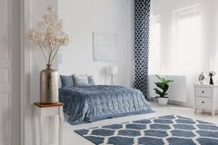 Fleurs dans le vase à or dans la chambre à coucher blanche intérieure avec le tapis modelé devant le lit bleu Photo réelle image libre de droits