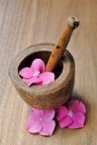 Fleurs dans un pilon en bois pour l'aromatherapy et la station thermale Photographie stock libre de droits