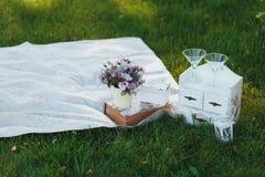 Fleurs dans un seau Pique-nique sur une herbe photographie stock