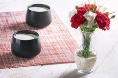 Fleurs dans un vase et des tasses avec du lait Image stock