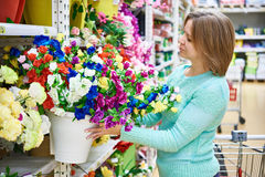 Fleurs de achat de femme dans le grand supermarché Photos stock