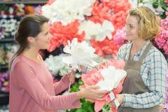 Fleurs de achat femelles dans le magasin Photographie stock