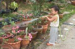 Fleurs de arrosage d'enfant en bas âge Photo stock