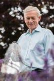 Fleurs de arrosage d'homme supérieur dans le jardin avec le tuyau Photo stock