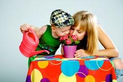 Fleurs de arrosage de maman et de fils avec une boîte d'arrosage Images stock