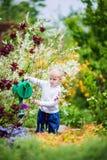 Fleurs de arrosage de petit jardinier Photo stock