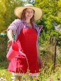 Fleurs de arrosage de femme dans le jardin Photo libre de droits