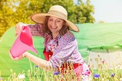 Fleurs de arrosage de femme dans le jardin Photos libres de droits
