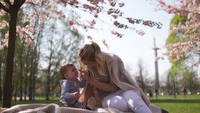 Fleurs de cerisier de Sakura - jeune m?re de maman s'asseyant avec son fils de b?b? de petit gar?on en parc ? Riga, Lettonie l'Eu banque de vidéos