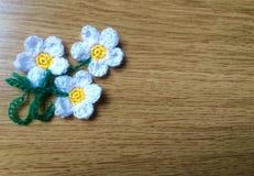 Fleurs de crochet sur la surface en bois Images stock