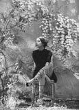 Fleurs de floraison sur extérieur beige La femme adorable s'asseyant sur la chaise en osier sous la floraison fleurit Images libres de droits