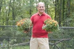 Fleurs de jardinage de propriétaire d'une maison mâle à l'extérieur Photographie stock libre de droits