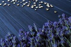 Fleurs de lavande et coeurs en bois d'amour sur une table en bois bleu-foncé Images libres de droits