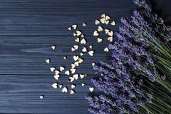 Fleurs de lavande et coeurs en bois d'amour sur une table en bois bleu-foncé Images stock