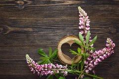 Fleurs de loup roses et coeur en bois décoratif sur en bois foncé Photo libre de droits