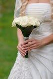 Fleurs de mariage dans des mains de jeune mariée photo stock