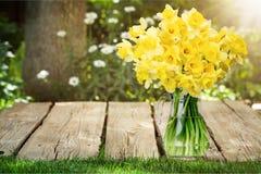Fleurs de narcisse dans le vase sur le fond en bois photo stock