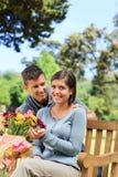 Fleurs de offre de jeune homme à sa amie Photos stock